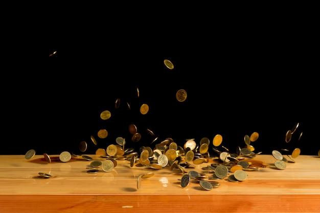 Dinheiro de moedas de ouro caindo na mesa de madeira