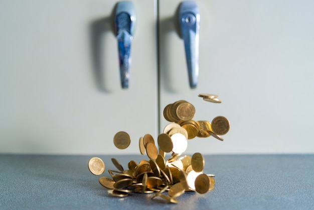 Dinheiro de moedas de ouro caindo na mesa do escritório