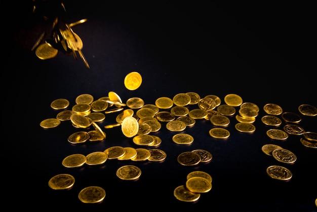 Dinheiro de moedas de ouro caindo no escuro