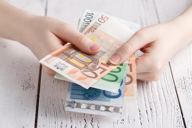 Dinheiro de notas de euro em mãos femininas