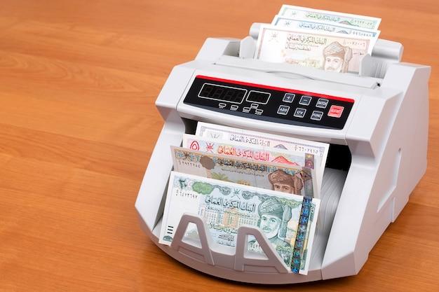 Dinheiro de omã em uma máquina de contagem