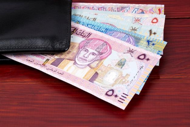 Dinheiro de omã - rial na carteira preta