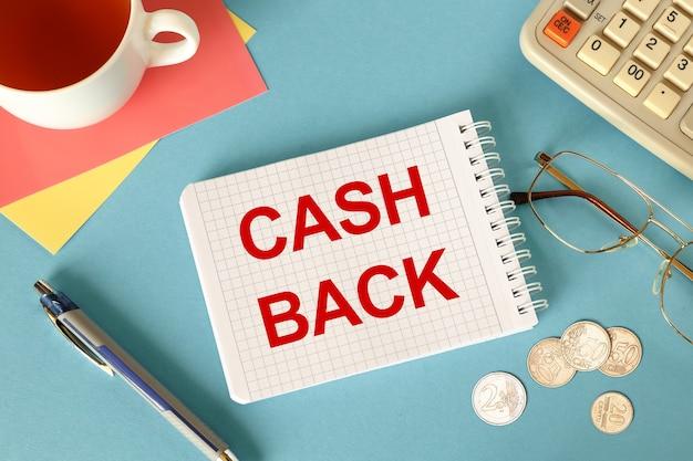 Dinheiro de volta está escrito em um bloco de notas em uma mesa de escritório com acessórios de escritório.