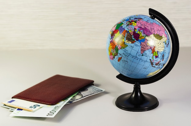 Dinheiro dentro do passaporte e globo