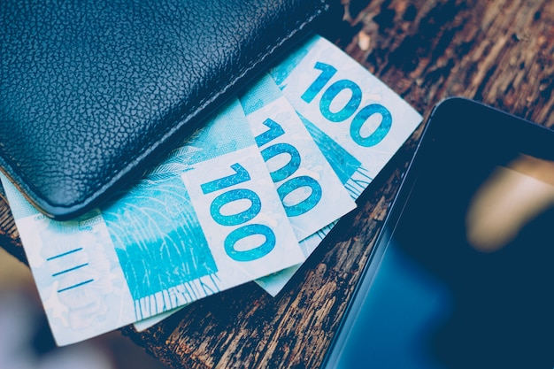 Dinheiro do brasil. notas reais, moeda brasileira dentro de uma carteira preta e celular ao lado. conceito de finanças, economia e riqueza.