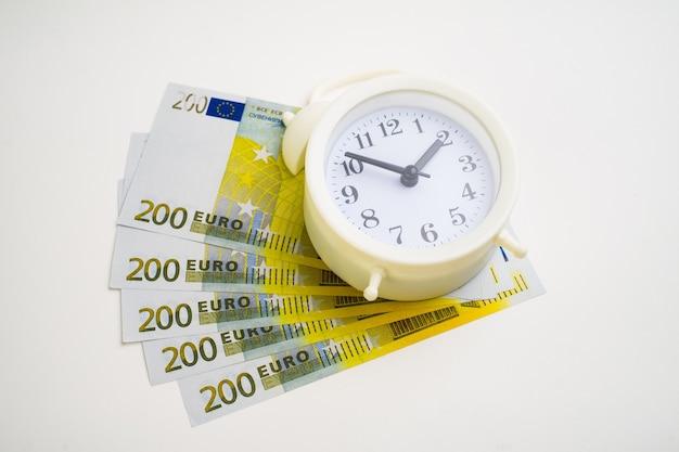 Dinheiro do euro do despertador com estilo retrô isolado no branco. tempo é conceito de dinheiro