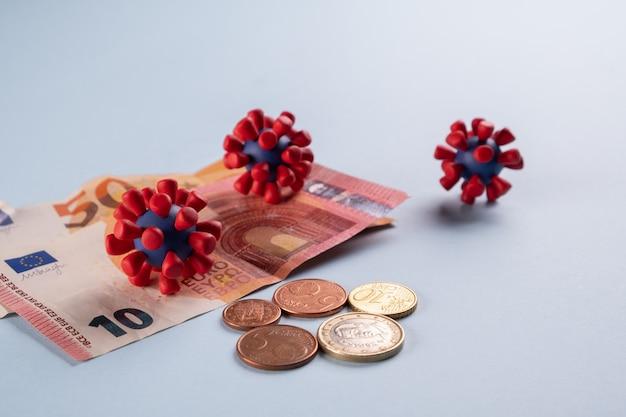 Dinheiro do euro, moedas e modelos de vírus da covid-19 dinheiro contaminado contaminado. crise econômica
