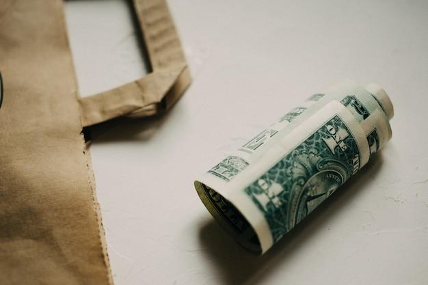 Dinheiro dos dólares do dinheiro, com um pacote de kraft no fundo textured branco.