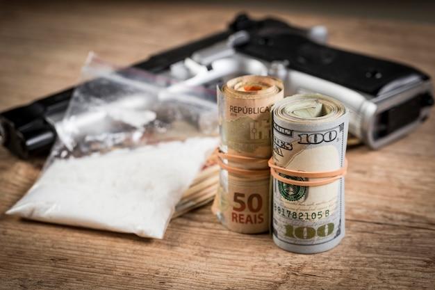 Dinheiro, drogas e uma arma em uma mesa de madeira