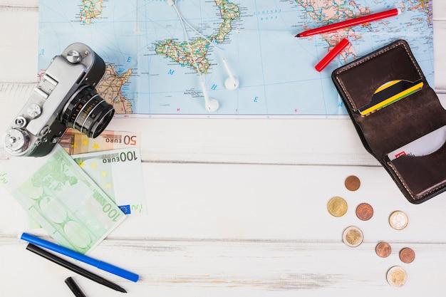 Dinheiro e acessórios para viajar na mesa