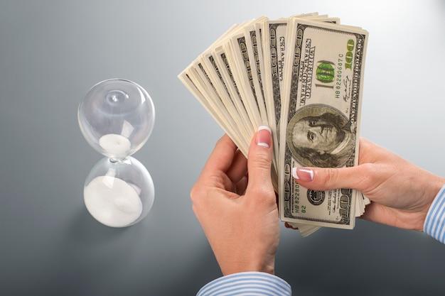 Dinheiro e ampulheta da mulher de negócios. senhora segurando dólares ao lado da ampulheta. deixe-me pensar. não faça escolhas espontâneas.