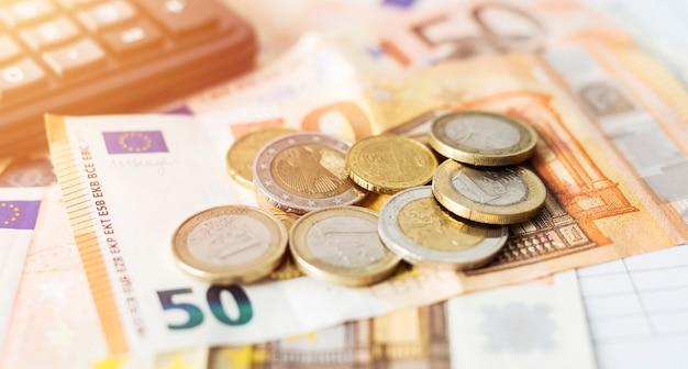 Dinheiro e calculadora de dados financeiros com gráficos e números.