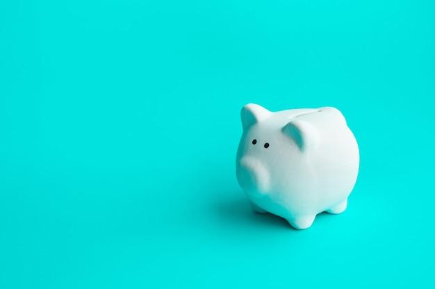Dinheiro e conceitos financeiros com cofrinho sobre fundo azul