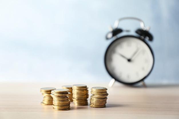 Dinheiro e despertador na mesa de madeira