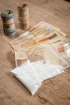 Dinheiro e drogas em uma mesa de madeira