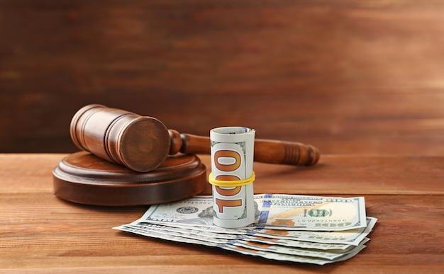 Dinheiro e martelo do juiz em fundo de madeira