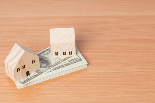 Dinheiro em dólares americanos com um modelo doméstico de madeira com fundo de madeira