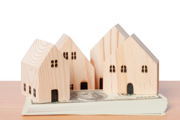 Dinheiro em dólares americanos com um modelo doméstico de madeira