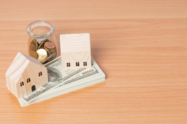 Dinheiro em dólares americanos e economizando moedas com um modelo doméstico de madeira com fundo de madeira