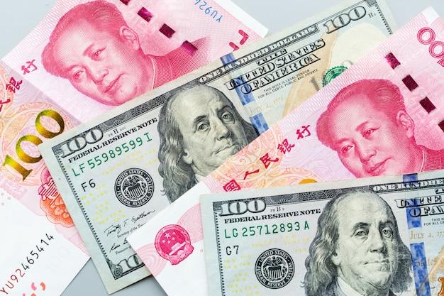 Dinheiro em espécie: cem dólares americanos e cem yuan chinês em cinza
