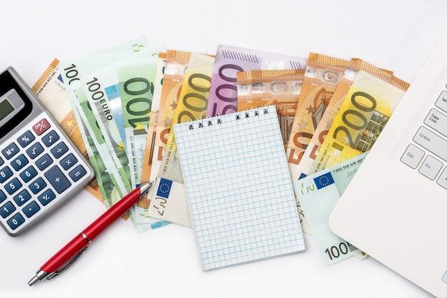 Dinheiro em euros, laptop e calculadora