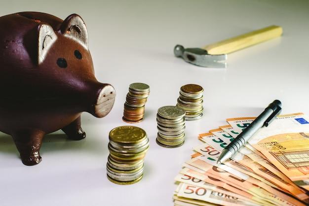 Dinheiro em moedas e contas ao lado de um cofrinho para salvar