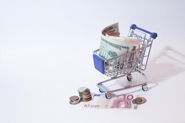 Dinheiro em uma cesta de supermercado em um fundo branco