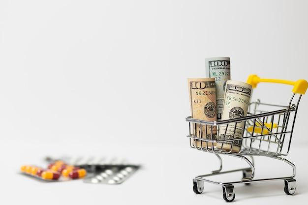 Dinheiro enrolado em um tubo em um carrinho em branco com comprimidos.