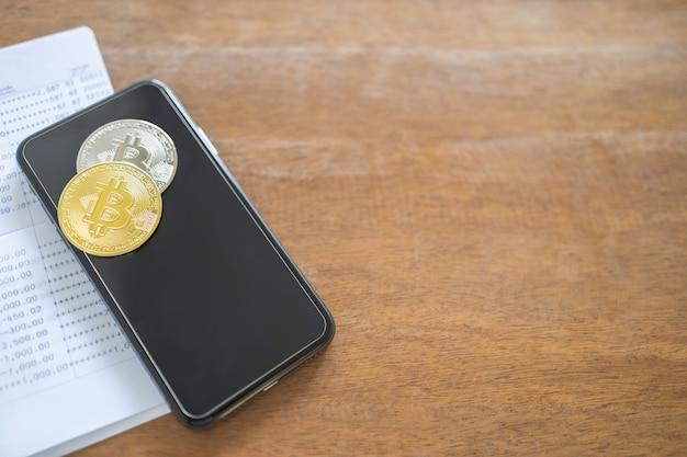 Dinheiro, finanças e conceito de criptomoeda. feche acima das moedas de ouro e prata de bitcoin no telefone móvel esperto e na caderneta bancária na tabela de madeira velha.
