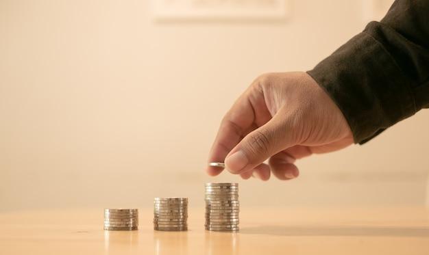 Dinheiro, financeiro, conceito do crescimento do negócio, a mão do homem põe moedas do dinheiro à pilha de moedas, negócio crescente.