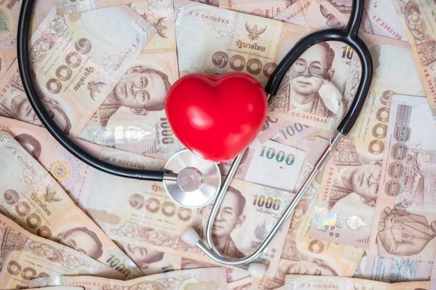 Dinheiro, forma de coração vermelho e estetoscópio de cardiologia