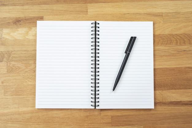 Dinheiro (moedas), calculadora e caderno, bloco de notas, caneta na mesa de madeira, vista superior com espaço de cópia
