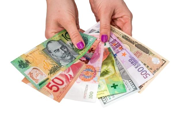 Dinheiro mundial diferente em mãos femininas isoladas na parede branca