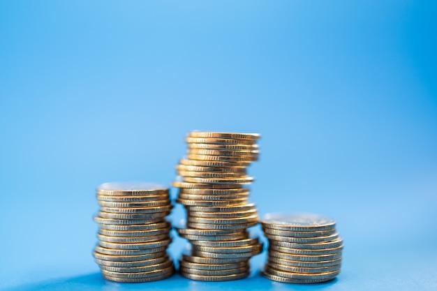 Dinheiro, negócios e conceito de risco. close up da pilha instável de moedas no fundo azul com espaço da cópia.