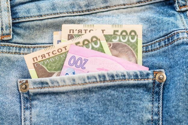 Dinheiro no bolso traseiro da calça jeans. fundo de textura de jeans. ucraniano quinhentos e duzentos hryvnia. notas de banco nacionais. conceito de finanças, economia e moda.