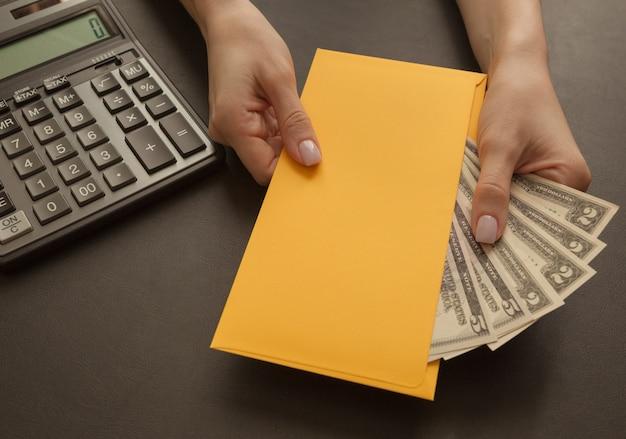 Dinheiro no envelope em mãos femininas