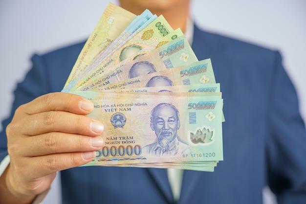 Dinheiro no vietnã segurar por lado homem de negócios vestindo um terno azul