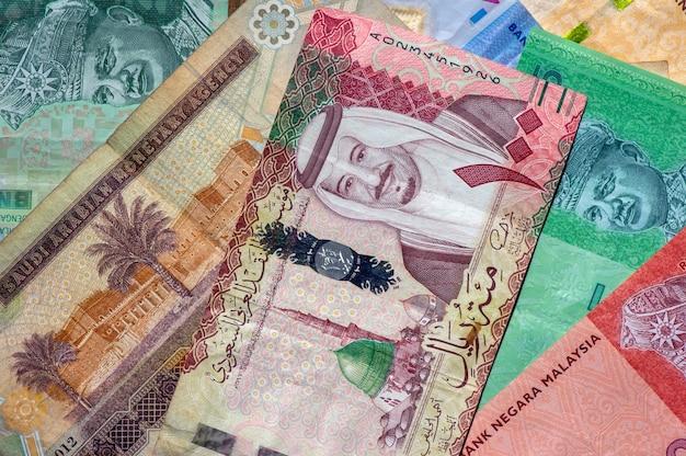 Dinheiro, notas de ringgit malaysia e riyals da arábia saudita para segundo plano. conceito de negócios, finanças, economia e investimento.