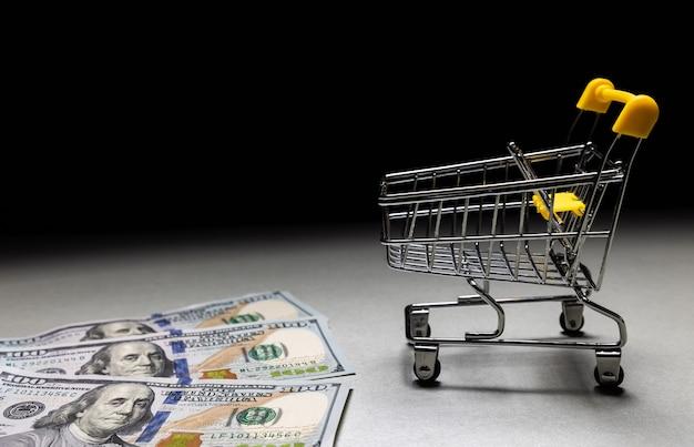 Dinheiro, notas, dólares estão perto da cesta de compras
