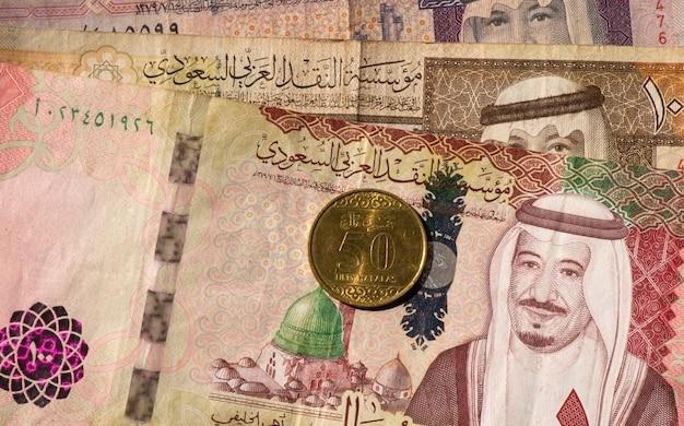 Dinheiro, notas e moedas de riais da arábia saudita em foco superficial
