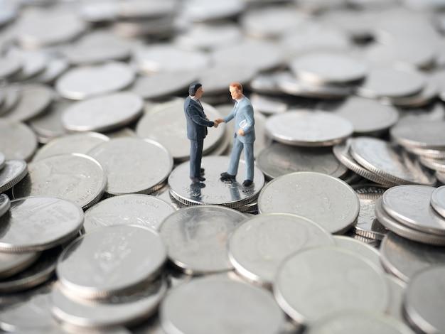 Dinheiro, pilha de moedas, aperto de mão de dois empresários em miniatura