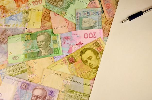 Dinheiro ucraniano, caneta e espaço em branco