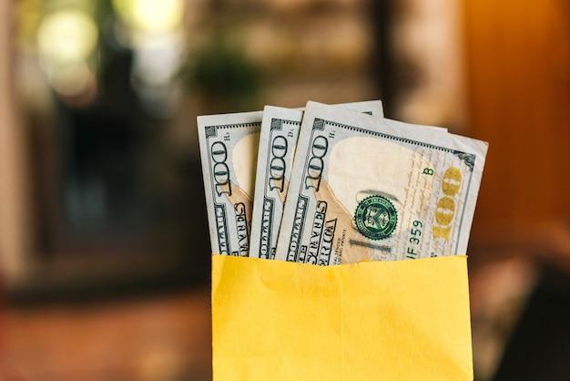 Dinheiro - uma mão segurando um envelope com notas de 100 dólares