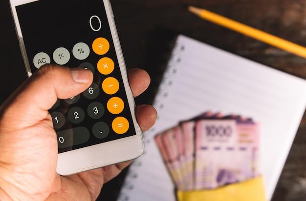 Dinheiro - uma mão segurando uma calculadora, notas, notas, pesos mexicanos