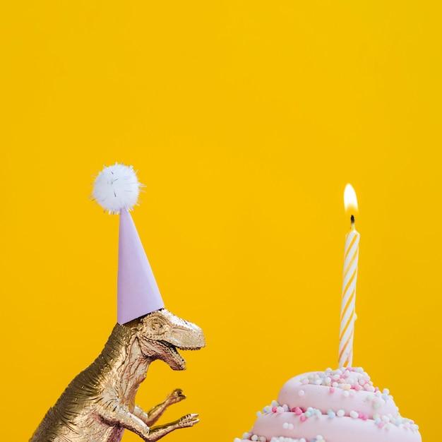 Dinossauro com chapéu de aniversário e delicioso bolinho