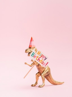 Dinossauro de brinquedo engraçado segurando placa de feliz aniversário