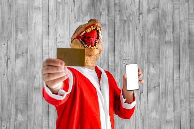 Dinossauro disfarçado de papai noel com cartão de crédito e celular na mão