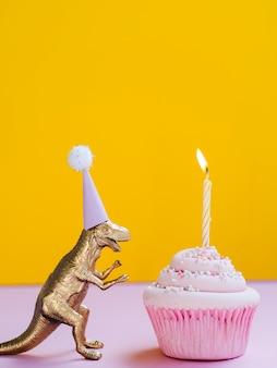 Dinossauro engraçado com chapéu de aniversário e delicioso bolinho