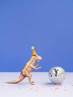 Dinossauro engraçado com chapéu de aniversário e globo de discoteca