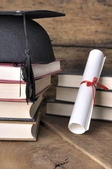 Diploma, chapéu e livros
